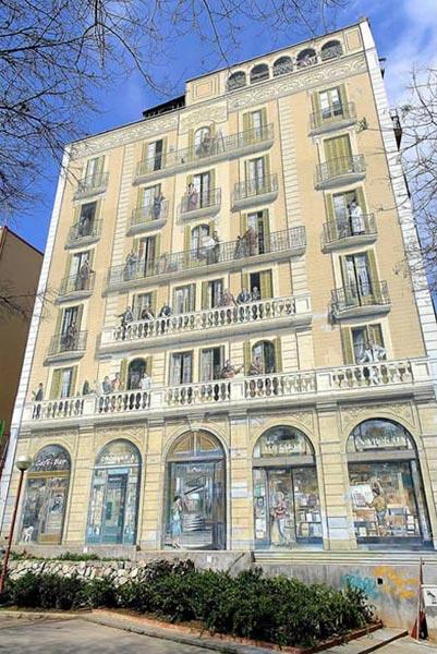 """2. Những ban công Barcelona là 1 kiệt tác nghệ thuật trải rộng trên 1 tòa nhà. Các nghệ sỹ đã dùng thuật """"đánh lừa thị giác"""" (trompe-l'oeil) để thể hiện tác phẩm hội họa này. Nó vẽ nên các quang cảnh đa dạng của cuộc sống thành thị giữa những khoảnh khắc khác nhau của lịch sử: từ Joaquim Blume, Cristóbal Colón, Santiago Rusiñol, Joan Miró, Pablo Picasso đến những cá nhân khác. Bức tường-tranh này được sáng tạo vào năm 1992."""