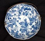 Chinese blue and white dish with a later Dutch silver handle Kangxi(1662-1722) diameter:10.5 in. ; 26.5 cm. Condition: dish pierced to accommodate silver handle and slight frits.