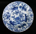 Chinese blue and white basin, Kangxi (1662-1722), decorated with central roundel with blossom issuing from rockwork, the cartouce divided into six panels with alternating precious objects and flowers and plants growing on a bank, diameter: 10 1/4in. 26.3cm., condition: small rim flake stuck back and minute frits