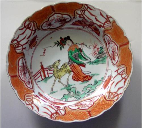 """Đĩa ngũ thái đời Khang Hy thể hiện Ma cô tiên nữ (Magu the fairy) mang một cành đào tiên, có một con nai làm bạn đồng hành. Trên nền vẽ bạn cũng thấy có nấm linh chi, tất cả là các biểu tượng về """"thọ"""""""