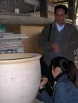 Anh Trần Quốc Thái đang hướng dẫn họa viên Tiểu Hạ sao chép hoa văn lên chiếc thống (chưa nung) tại Cảnh Đức Trấn.