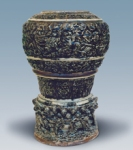 Chân đèn (phần dưới), lam xám và nâu    Phần dưới chân đèn tạo dáng mai bình. Trang trí nổi các băng cánh sen, rồng mây trong hoa lá. Men lam xám và nâu. Triều Lê Trung Hưng, thế kỷ 17. Vỡ miệng, sửa lại. C: 38,5cm.
