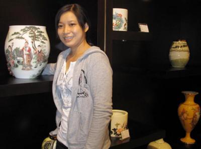 Một khách tham quan thích thú với các mẫu bình sứ có họa tiết sinh động, thanh thoát đã tạo dáng chụp ảnh lưu niệm tại show room của Công ty Minh Long 1.