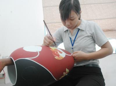 Tại xưởng vẽ, nữ nghệ nhân đang trổ tài sáng tạo các họa tiết trên thành bình đã được nung 1.380 độ C