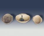 Ba chén hình ô van có 2 tai, gờ miệng phẳng, thành cong, đế bằng để mộc. Men trắng nhạt. Chiếc ở giữa có đọng giọt men xanh. Kiểu Hán, thế kỷ 1-3. Sứt miệng. C: 2,6cm - 3cm; Đkm: 8,4cm - 10,2cm.