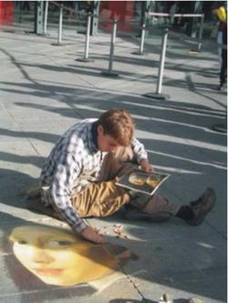 Một họa sĩ trẻ đang hành nghề bên ngoài  trung tâm triển lãm Pompidou