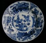 Chinese blue and white dish, Kangxi (1662-1722), d Ref: Q903 Chinese blue and white dish, Kangxi (1662-1722), decorated with peonies growing from rocks within four-panel border of flowers, rocks and Buddhistic motifs, diameter: 15.8cm. Condition: base rim drilled with hole for hanging